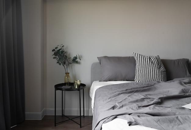 Ustawienie narożnych sypialni miękkich poduszek ozdobionych okrągłym stolikiem nocnym i złotą ramą na beżowej ścianie