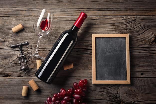 Ustawienie obiadowe z czerwonego wina i prezent na rustykalnym drewnie. widok z góry z miejscem na pozdrowienia.