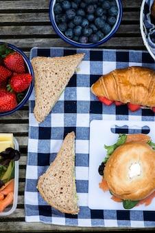 Ustawienie piknikowe z różnymi kanapkami i jagodami