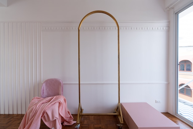 Ustawienie różowego krzesła z różowym bieżnikiem na łóżku ze złotym prętem działowym i pomalowaną na biało ścianą