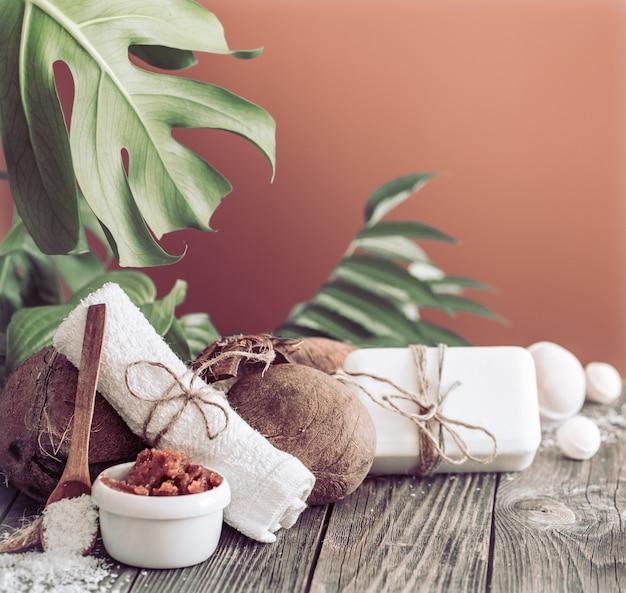 Ustawienie spa i odnowy biologicznej z kwiatami i ręcznikami. jasna kompozycja na brązowym stole z tropikalnymi kwiatami. produkty natury dayspa z kokosem