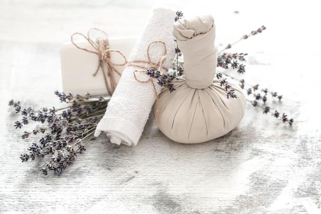 Ustawienie spa i odnowy biologicznej z kwiatami i ręcznikami. jasna kompozycja z kwiatami lawendy. produkty natury dayspa z kokosem