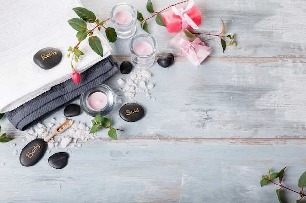 Ustawienie spa na niebieskim drewnianym stole w stylu rustykalnym. naturalna sól morska, świece, ręcznie robione mydło, kwiaty, ręczniki. skład terapii uzdrowiskowej, koncepcja spa. widok z góry
