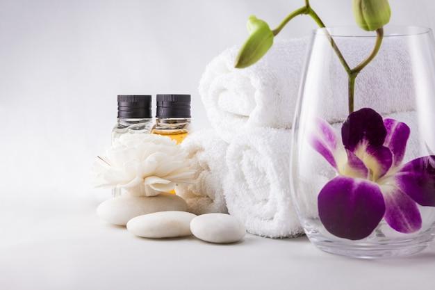 Ustawienie spa z ręcznikami butelki olejku zapachowego orchidei i ręcznie robiony kwiat w saunie.