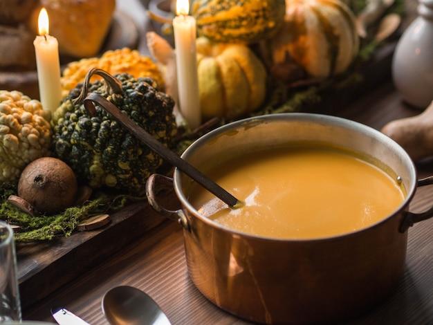 Ustawienie stołu na święto dziękczynienia. duża patelnia miedziana z pomarańczową zupą dyniową.