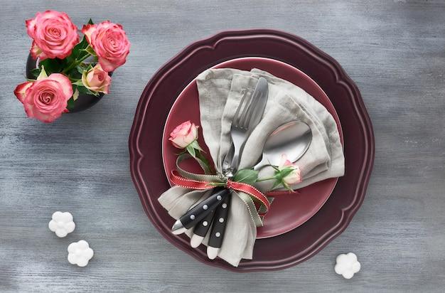 Ustawienie stołu na urodziny lub rocznicę walentynek, widok z góry na szaro. różowe róże, ciemnoczerwone talerze, serwetka i naczynia, ozdobione pączkiem róży i wstążkami.