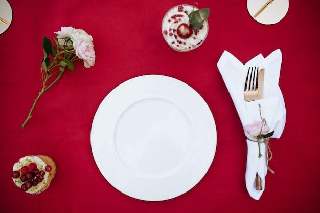 Ustawienie stołu, przyjęcie herbaciane ze świeżym ciastem jagodowym, widok z góry, nikt. luksusowe sztućce na czerwonym obrusie, zastawa stołowa na zewnątrz.