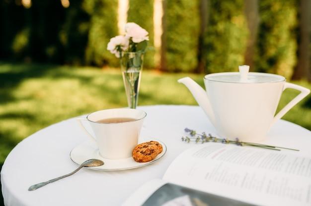 Ustawienie stołu, romantyczna impreza herbaciana ze słodyczami, nikt. luksusowe sztućce na białym obrusie, zastawa stołowa na zewnątrz.