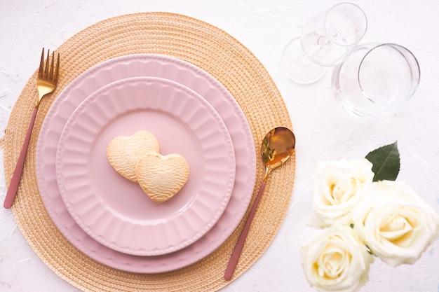 Ustawienie stołu. serwetka wiklinowa, dwa różowe talerze, biszkoptowe serce
