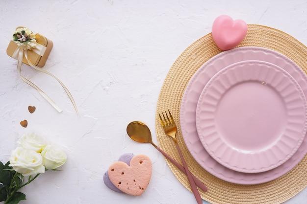 Ustawienie stołu. serwetka wiklinowa, dwa różowe talerze