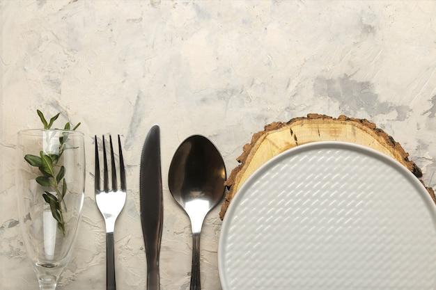 Ustawienie stołu. sztućce. kieliszek do wina, widelec, nóż w białej serwetce i talerz na drewnianym stojaku na jasnym betonowym stole. widok z góry