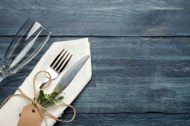 Ustawienie stołu. sztućce. kieliszek do wina widelec, nóż w białej serwetce na niebieskim drewnianym stole. widok z góry