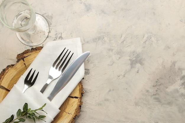 Ustawienie stołu. sztućce. szkło, widelec, nóż w białej serwetce i drewniany stojak na jasnym betonowym stole. widok z góry