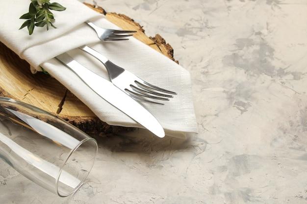Ustawienie stołu. sztućce. szkło, widelec, nóż w białej serwetce i drewniany stojak na jasnym betonowym stole.