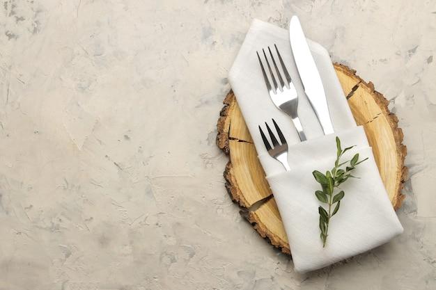Ustawienie stołu. sztućce. widelec, nóż w białej serwetce i drewniany stojak na jasnym betonowym stole. widok z góry