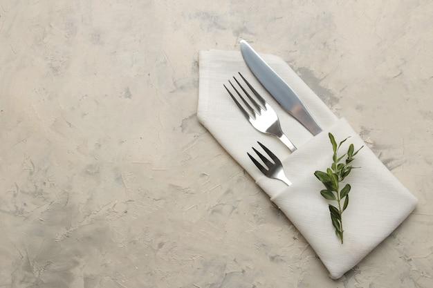 Ustawienie stołu. sztućce. widelec, nóż w białej serwetce na jasnym betonowym stole. widok z góry