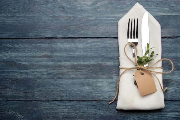 Ustawienie stołu. sztućce. widelec, nóż w białej serwetce na niebieskim drewnianym stole. widok z góry