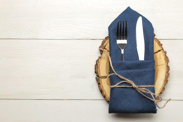 Ustawienie stołu. sztućce. widelec, nóż w niebieskiej serwetce i drewniany stojak na białym drewnianym stole. widok z góry