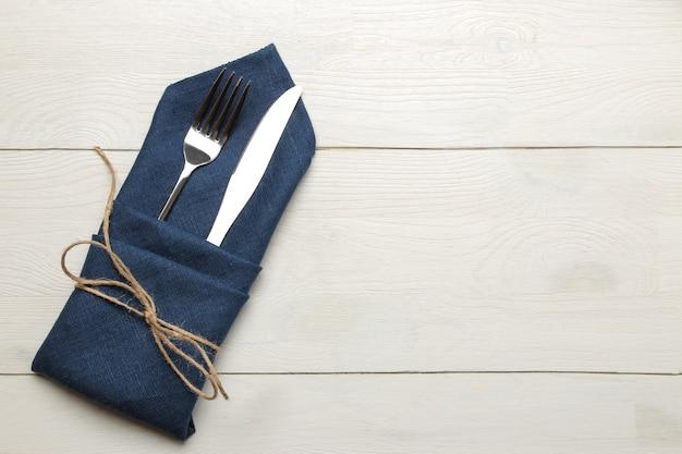 Ustawienie stołu. sztućce. widelec, nóż w niebieskiej serwetce na białym drewnianym stole. widok z góry