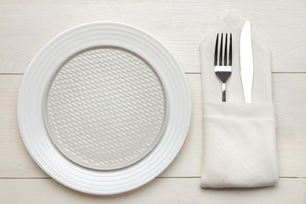 Ustawienie stołu. sztućce. widelec, nóż w serwetce i talerz na białym drewnianym stole. widok z góry