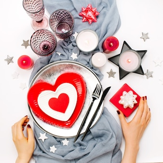 Ustawienie stołu walentynki. kobiece ręce trzymają prezent. białe i czerwone naczynia w formie serca, szklanki do napojów, świece i sztućce na białym tle. romantyczna koncepcja