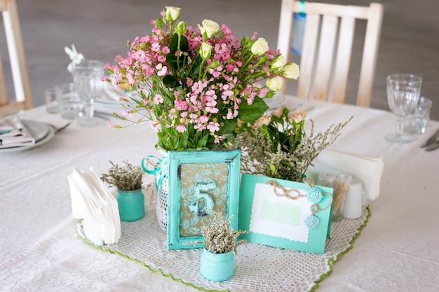 Ustawienie stołu weselnego z kwiatami i liczbą.