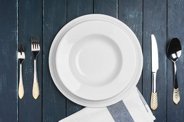 Ustawienie stołu z talerzami na ciemnym drewnianym stole