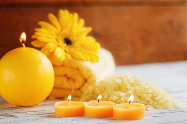 Ustawienie żółtych produktów spa. morze sól, ręcznik i świeczki na ciemnym drewnianym tle