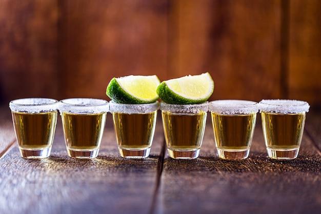 Ustawiono kilka szklanek tequili, napoju kultury meksykańskiej, zrobionego z destylowanego alkoholu, cytryny, soli i niebieskiej agawy. międzynarodowy dzień tequili. kopia tekstu.