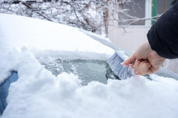 Usuwanie śniegu z przedniej szyby samochodu szczotką samochodową