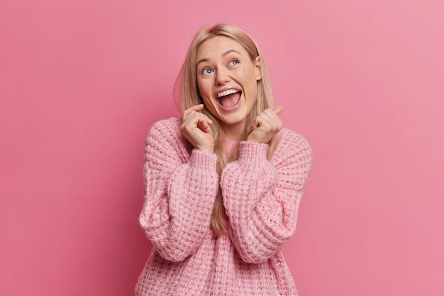 Uszczęśliwiona blondynka młoda kobieta ma radosny wyraz twarzy, który wygląda powyżej, trzyma usta otwarte, ubrana w zwykłe ubranie