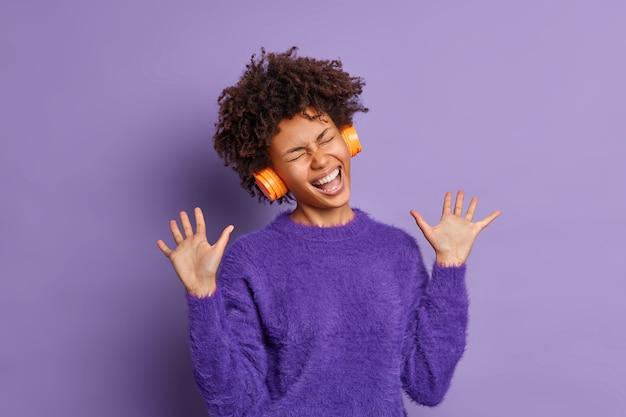 Uszczęśliwiona ciemnoskóra kobieta śpiewa piosenkę głośno unosi dłonie ma przesadny wyraz twarzy nosi słuchawki na uszach do słuchania muzyki ubrana w swobodny sweter