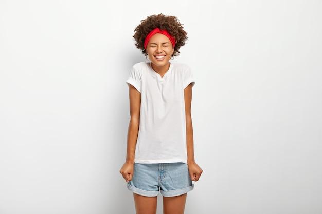 Uszczęśliwiona ciemnoskóra kobieta z włosami afro trzyma dłonie zaciśnięte w pięści, cieszy się długo oczekiwanymi wakacjami, ubrana w swobodny letni strój, wyraża dobre emocje, na białym tle