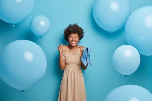 Uszczęśliwiona kobieta cieszy się, że w prezencie od chłopaka dostała buty jej wymarzonych, ubrana jest w długą beżową sukienkę koktajlową, z radością zaciska pięść, wybiera najlepszy strój na bal maturalny. kobiety, ubrania, świętowanie