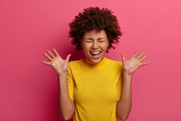 Uszczęśliwiona, optymistyczna dziewczyna milenialsów śmieje się i unosi dłonie, ma bardzo radosny wyraz twarzy, ogląda zabawną scenę, ubrana w żółtą koszulkę, odizolowaną na różowej ścianie. koncepcja pozytywnych emocji