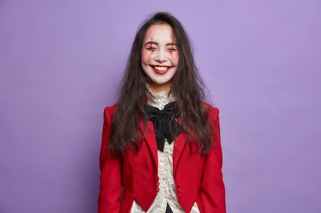 Uszczęśliwiona, szczęśliwa kobieta duch świętuje halloween, ubrana w okropny makijaż, ubrana w kostium karnawałowy na fioletowej ścianie
