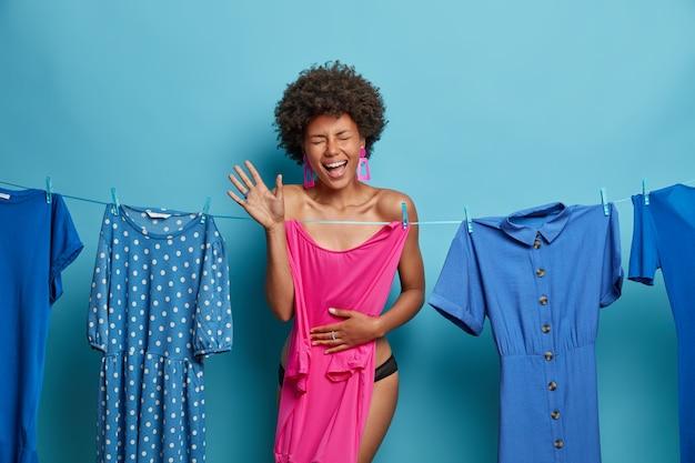 Uszczęśliwiona szczupła ciemnoskóra kobieta stoi rozebrana, chowa się za różową sukienką, wybiera strój, pozuje na niebieskiej ścianie z różnymi sukienkami wiszącymi na linie. ludzie, odzież, koncepcja ubioru