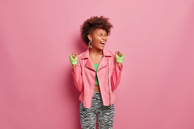 Uszczęśliwiona szczupła kobieta ma afro fryzury z radością pięści, czuje się bardzo szczęśliwa i szczęśliwa po treningu na siłowni