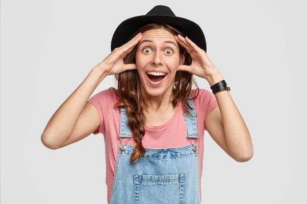 Uszczęśliwiona włoszka wpatruje się w zaskoczoną, radosną minę, trzyma ręce na głowie, nosi czarną czapkę i dżinsowe ogrodniczki, otrzymuje dobre wieści od rozmówcy. ludzie, emocje, styl