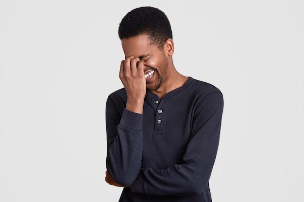 Uszczęśliwiony afro amerykanin śmieje się radośnie z czegoś śmiesznego, mruży twarz, ciesząc się, słyszy zabawny żart od przyjaciela, ubrany w czarny przypadkowy sweter, ma ciemną skórę, na białym tle