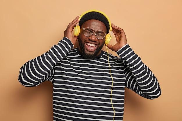 Uszczęśliwiony brodacz trzyma ręce na słuchawkach, nosi sweter w paski