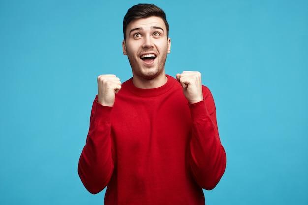 Uszczęśliwiony, ekstatyczny, szczęśliwy młody mężczyzna rasy kaukaskiej z włosiem, cieszący się sukcesem