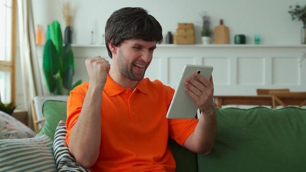 Uszczęśliwiony mężczyzna siedzi na sofie i czuje euforyczny triumf czytając dobre wieści na nowoczesnym tablecie