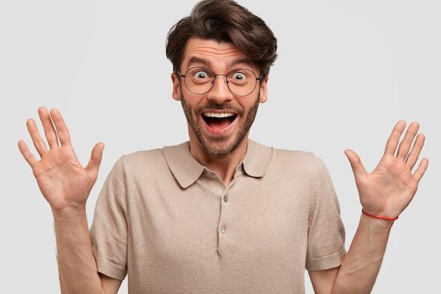 Uszczęśliwiony, nieogolony mężczyzna trzyma splecione dłonie, ma radosny wyraz twarzy, raduje się dobrą nowiną otrzymaną od krewnych, ubrany w swobodną koszulkę, odizolowany na białej ścianie