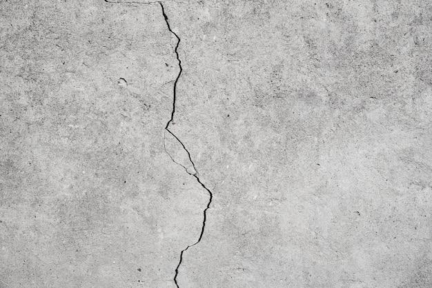 Uszkodzona ściana. szare tło z pęknięciem
