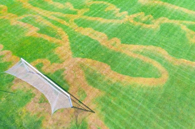 Uszkodzona trawa trawnikowa na boisku piłkarskim. widok z drona. nieprawidłowe stosowanie nawozów mineralnych lub herbicydów. wandalizm na boisku sportowym.