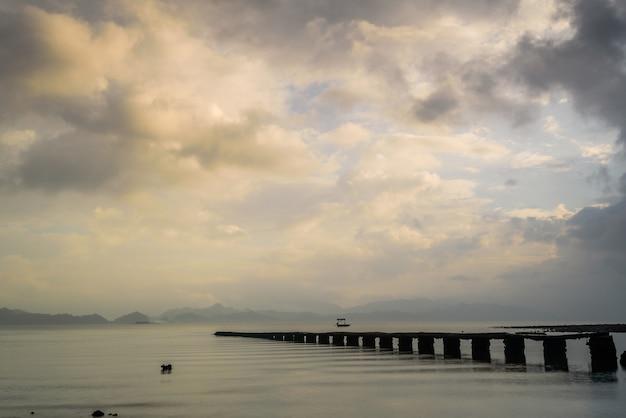 Uszkodzone molo na jeziorze podczas wschodu słońca w hongkongu