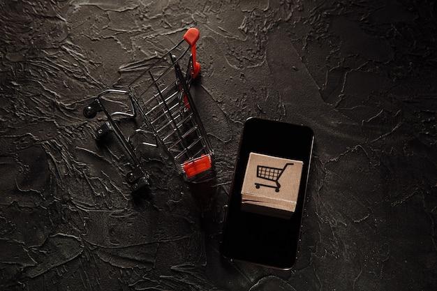 Uszkodzone pudełko papierowe i smartfon. koncepcja zakupów i dostawy online. wypadek podczas transportu