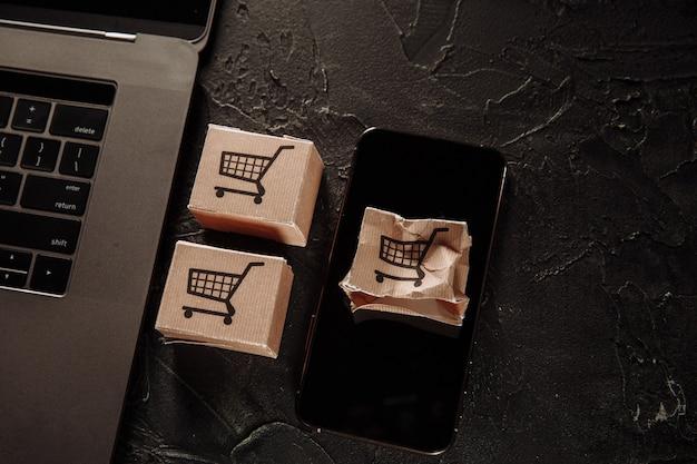 Uszkodzone pudełko papierowe na ekranie smartfona. koncepcja zakupów i dostawy online