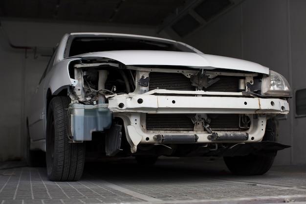 Uszkodzony biały samochód w garażu